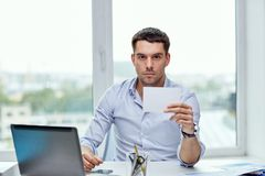 Businessman showing blank paper card at office Stock Image
