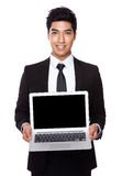 Businessman showing the blank screen of laptop computer. Isolated on white background royalty free stock photo