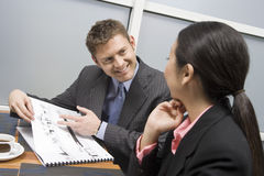 Businessman Showing Blueprints To His Female Business Partner Stock Images