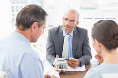 Businessman showing calculator to his clients. In an office royalty free stock image