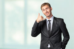 Businessman showing Call me sign Royalty Free Stock Images