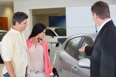 Businessman showing a car to a couple Royalty Free Stock Photo