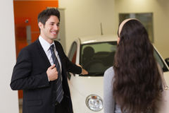 Businessman showing a car to a woman Royalty Free Stock Image