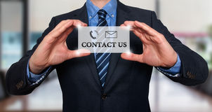 Businessman showing card with Contact Us text Stock Image