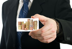 Businessman showing card with stack of coins Royalty Free Stock Images