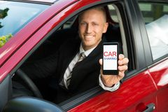 Businessman showing cellphone with car sharing text on screen. Happy Businessman Sitting In Car Showing Cellphone With Car Sharing Text On Screen Stock Photos