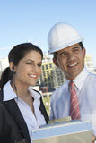 Businessman Showing Clipboard To Businesswoman With Earpiece Stock Photo