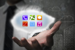 Businessman showing colorful app icons on cloud with doodles wal Royalty Free Stock Photography