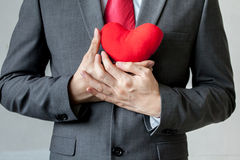 Businessman showing compassion holding red heart onto his chest. In his suit - crm, service mind business concept royalty free stock photo