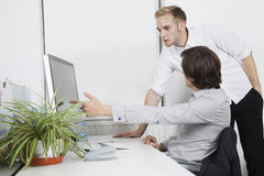 Businessman showing computer screen to coworker at desk Royalty Free Stock Photography