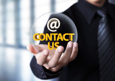 Businessman showing contact us text in crystal ball Royalty Free Stock Photos