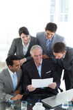 Businessman showing a contract to his team Stock Photo
