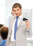 Businessman showing credit card in office Royalty Free Stock Images
