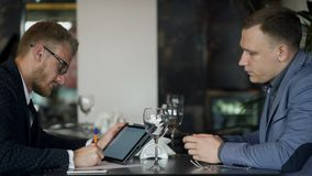 Businessman showing data on the tablet to the investor during lunch. Businessman showing data on the tablet to the investor during lunch stock footage