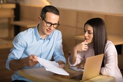 Businessman showing documents to businesswoman stock images