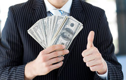 Businessman showing dollars with thumbs up Royalty Free Stock Photos