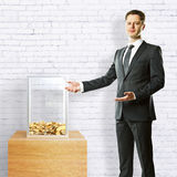 Businessman showing donation box. Young businessman in suit showing donation box on white brick background. 3D Rendering Stock Image