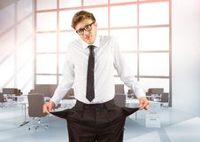 Businessman showing empty pockets while standing in office. Digital composite of Businessman showing empty pockets while standing in office Royalty Free Stock Images