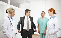 Businessman showing empty pockets to doctors. No money for health: Businessman showing empty pockets to doctors Royalty Free Stock Photography
