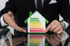 Businessman Showing Energy Efficient Chart On House Model. Cropped image of businessman showing energy efficient chart on house model in office stock image