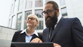 Businessman showing female investor development project presentation on tablet