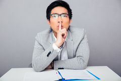 Businessman showing finger over lips. Be quiet!!!. Asian businessman in glasses showing finger over lips and looking at camera. Be quiet Stock Photo
