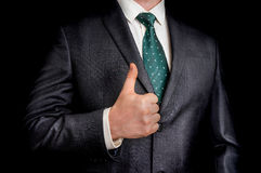 Businessman showing gesture with thumb up. On black background Royalty Free Stock Photography
