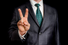 Businessman showing gesture victory with two fingers. On black background Stock Photography