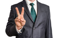 Businessman showing gesture victory with two fingers. Isolated on white background Stock Photography