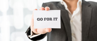 Businessman Showing Go For it Message on a Card. Close up Businessman Showing Conceptual Go For it Message on a Small White Card Royalty Free Stock Photo