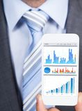 Businessman showing graphs on smartphone Stock Photo