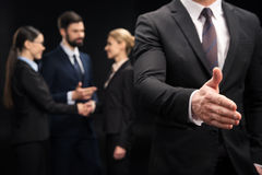 Businessman showing handshake sign while business people connecting behind him Stock Photography
