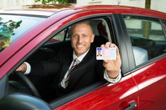 Businessman showing his driving license Royalty Free Stock Images