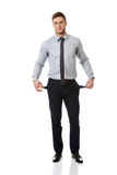 Businessman showing his empty pockets. Royalty Free Stock Image