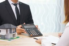 Businessman showing the home price on calculator and customer re. Ady to sign loan contract stock photo