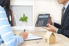 Businessman showing the home price on calculator and customer re. Ady to sign loan contract stock photography