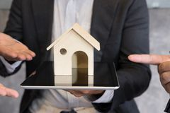 Businessman showing house model on digital tablet. Realtor offer Royalty Free Stock Photography