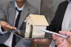 Businessman showing house model on digital tablet. Realtor offer Stock Photo