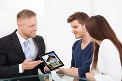 Businessman showing house picture to couple on tablet Stock Photography