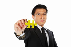 Businessman showing jigzaw puzzle piece royalty free stock images
