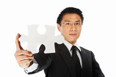 Businessman showing jigzaw puzzle piece Royalty Free Stock Image