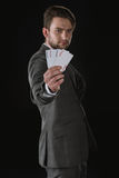 Businessman showing Joker cards isolated on black Stock Image