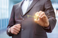 Businessman showing a key to success . Businessman showing a key to success on blurred background Stock Photo