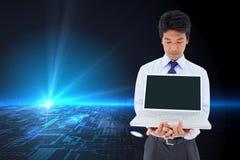 Businessman showing a laptop. Composite image of portrait of a young businessman showing a laptop stock images