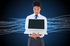 Businessman showing a laptop. Composite image of portrait of a young businessman showing a laptop royalty free stock image