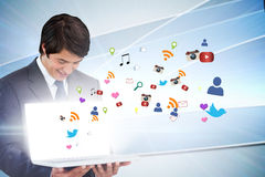 Businessman showing laptop with app icons Royalty Free Stock Photos