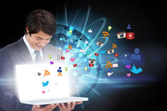 Businessman showing laptop with app icons Royalty Free Stock Images