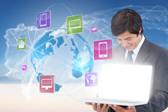 Businessman showing laptop with app icons Royalty Free Stock Photo