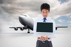 Businessman showing a laptop. Composite image of portrait of a young businessman showing a laptop stock photo