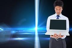 Businessman showing a laptop. Composite image of portrait of a young businessman showing a laptop stock photos